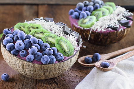 Açai smoothie bowl with fresh kiwi, frozen blueberries, organic coconut and dark chocolate pieces with wooden spoons served in coconut bowls over a rustic table. Selective focus with blurred background.
