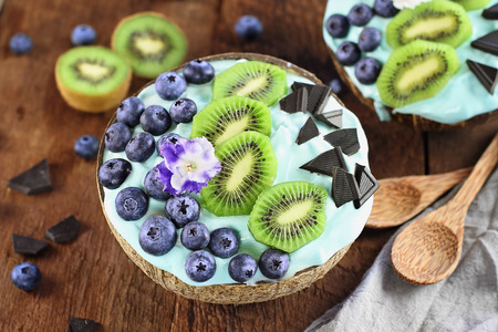 Blue spirulina and berry smoothie bowl, fresh blueberries, kiwi and chocolate pieces with wooden spoons served in coconut bowls over a rustic background. Image shot from above  overhead.