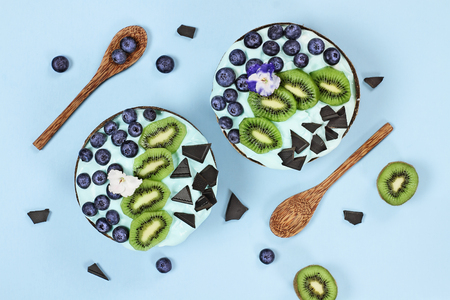Blue spirulina and berry smoothie bowl, fresh blueberries, kiwi and chocolate pieces with wooden spoons served in coconut bowls over a blue background. Image shot from above  overhead. Stock Photo