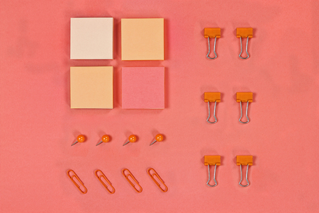 Variety of note pad paper, push pins and paper clips for organizing over coral color background with free space for text. Image shot from above.