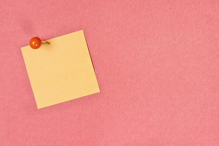 Blank yellow note pad paper over coral color background with free space for text. Image shot from above.