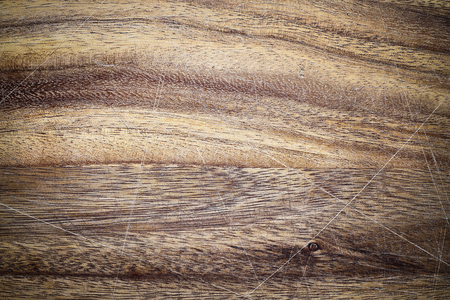 Vintage wooden cutting board with scratches and vignette. Image shot from above in flat lay position.