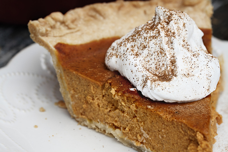 Slice of homemade pumpkin pie with topping and sprinkled with pumpkin pie spice. Extreme shallow depth of field with selective focus on whipped cream.