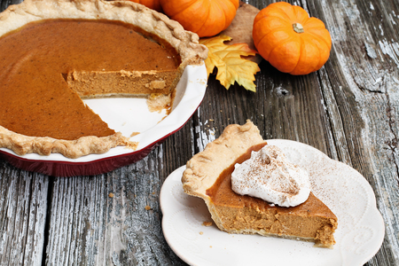 Slice of homemade pumpkin pie over a rustic wooden background. Extreme shallow depth of field with selective focus. Stock Photo