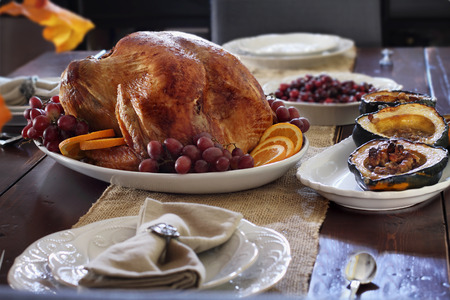 Delicious golden roasted Thanksgiving turkey  on a platter garnished with fresh grapes and slices of oranges on a rustic farmhouse table. Stock Photo