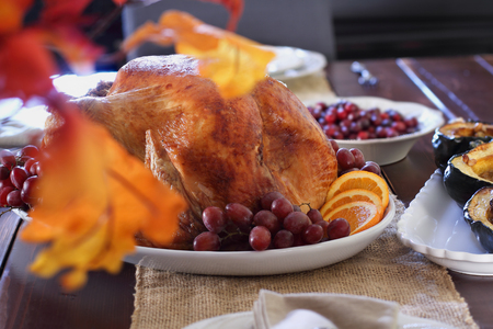 Family dining room table set with raost stuffed turkey for Thanksgiving Day. Selective focus on turkey.