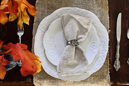 Thanksgiving Day or autumn place setting with napkins and cutlery over burlap table runner over a rustic farmhouse table background. Fall colorful leaves blurred in the foreground. Stock Photo