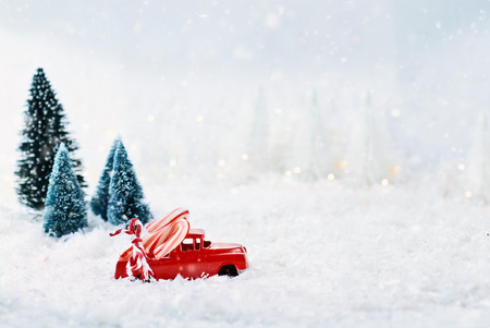 1950s antique vintage red truck hauling a candy canes home through a snowy winter wonder land with pine trees in background. Extreme shallow depth of field with selective focus on vehicle. Stock Photo