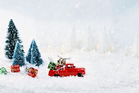 1950s antique vintage red truck hauling a Christmas gifts home through a snowy winter wonder land with pine trees. Extreme shallow depth of field with selective focus on vehicle. Stock Photo