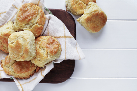 Fresh buttermilk southern biscuits or scones over a white table shot from above. Top view. Stock Photo