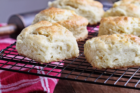 Freshly baked buttermilk southern biscuits or scones from scratch cooling on a cooling rack.