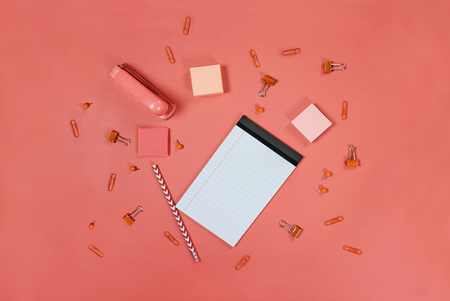 Blank white note pad paper, pencil, stapler, thumb tacks, paper clips, and adhesive paper over coral color background with free space for text. Image shot from top view. Stock Photo