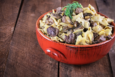 Venison or Beef Mushroom Stroganoff with in a red ceramic serving bowl garnished with fresh dill over a rustic wood table background. Stock Photo