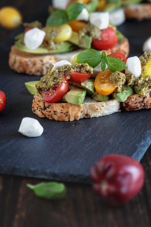 Avocado toast sandwich with avocados, pesto, mozzarella cheese, fresh from the garden basil and heirloom tomatoes, over a rustic wooden background. Greek food and healthy vegetarian diet concept. Stock Photo