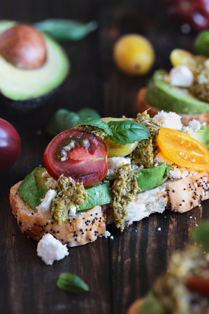 Avocado toast sandwich with avocados, pesto, fetaa cheese, fresh from the garden basil and heirloom tomatoes, over a rustic wooden background. Greek food and healthy vegetarian diet concept. Stock Photo