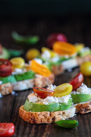 Avocado toast sandwich with avocados, fresh from the garden heirloom tomatoes and feta cheese, Greek food and healthy vegetarian diet concept, over a rustic wooden background with room for text.