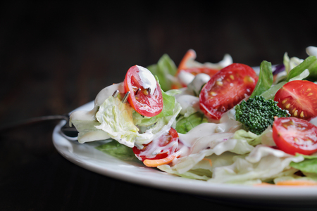Forkful and plate of homemade fresh salad with buttermilk ranch dressing, tomatoes, broccoli, cabbage and carrots served over a rustic wooden table. House Salad.