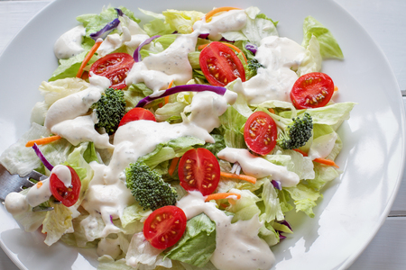 Plate of homemade fresh salad with buttermilk ranch dressing, tomatoes, broccoli, cabbage and carrots served over a white wooden table. House Salad. Shot from top view.