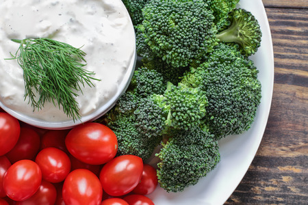 Homemade buttermilk ranch salad dressing with dill served with fresh cherry tomatoes and broccoli over a rustic wooden background. Image shot above from top view.