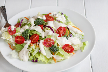 Plate of homemade fresh salad with buttermilk ranch dressing, tomatoes, broccoli, cabbage and carrots served over a white wooden table. House Salad.