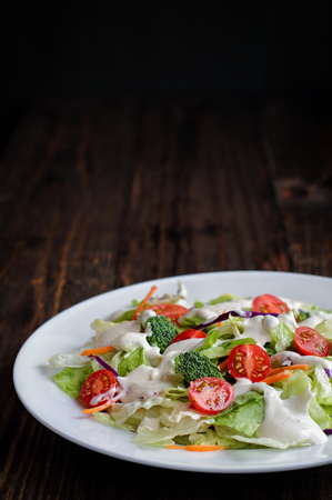 Plate of homemade fresh salad with buttermilk ranch dressing, tomatoes, broccoli, cabbage and carrots over a rustic wooden table and dark background. House Salad. Stock Photo