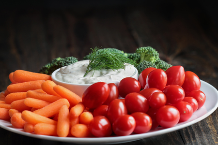 Homemade buttermilk ranch salad dressing with dill served with fresh vegetables, cherry tomatoes, baby carrots and broccoli, over a rustic wooden background.
