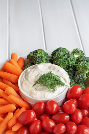 Homemade buttermilk ranch salad dressing with dill served with fresh vegetables, cherry tomatoes, baby carrots and broccoli, over a rustic white wooden table background with room for text.