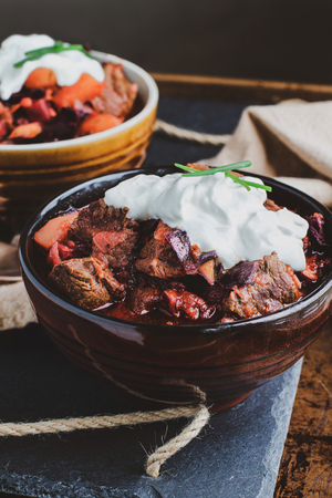Two bowls of Borscht soup with hearty, meaty chunks of beef, root vegetables, cabbage and beets. Served with sour cream and chives,