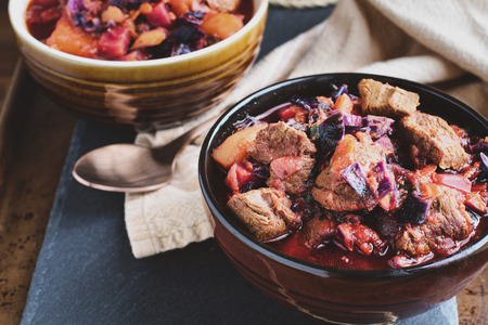 Bowl of Borscht soup with hearty, meaty chunks of beef, root vegetables, cabbage and beets. High angle view.