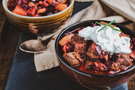 Two bowls of Borscht soup with hearty, meaty chunks of beef, root vegetables, cabbage and beets. Served with sour cream and chives,  High angle view.