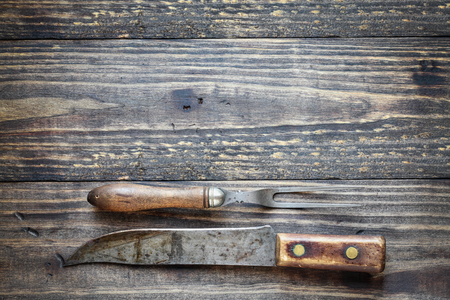 Antique meat fork and butchers knife over top a rustic wood table  background. Image shot from overhead view.
