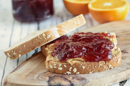 Homemade Peanut Butter and Jelly Sandwich on oat bread, over a rustic wooden background with fruit in the background ready for lunch.