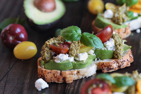 Avocado toast sandwich with avocados, pesto, feta cheese, fresh from the garden basil and heirloom tomatoes, over a rustic wooden background. Greek food and healthy vegetarian diet concept. Stock Photo