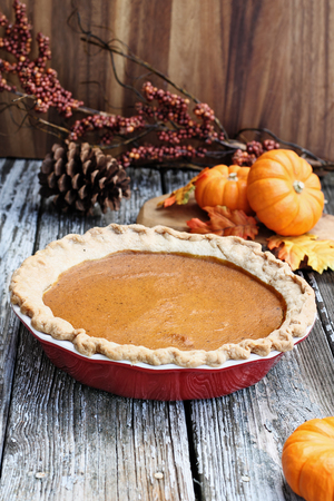 Homemade pumpkin pie in red ceramic pie plate over a rustic wooden background. Extreme shallow depth of field with selective focus.