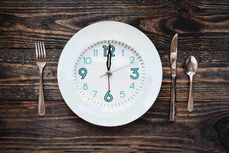 Twelve hour intermittent fasting time concept with clock on plate over a rustic wooden table  background. Top view.  Stock Photo