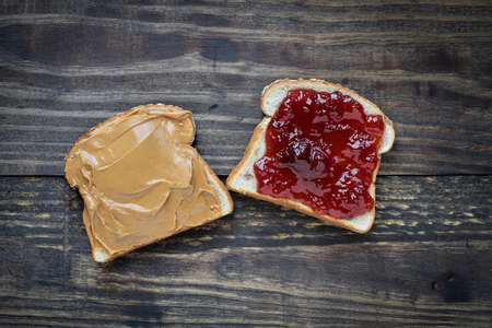 Top view of open face homemade peanut butter and strawberry Jelly sandwich on oat bread, over a rustic wooden background.