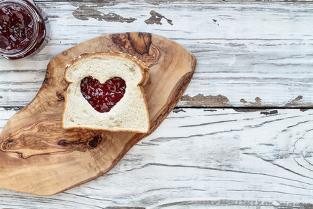 Top view of homemade peanut butter and jelly sandwich over a cutting board on a white rustic white wooden table  background with cut out heart center. Top view.