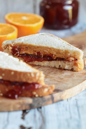 Homemade sliced peanut butter and jelly sandwich on oat bread, over a rustic wooden background ready for lunch. Selective focus with on center of sandwich with blurred foreground and background.
