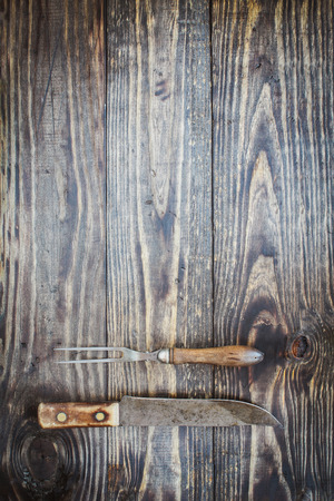 Vintage meat fork and butchers knife over top a rustic wood table  background. Image shot from overhead view.