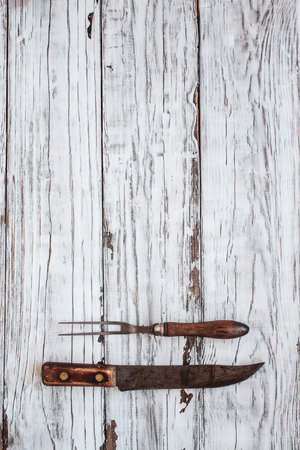 Vintage meat fork and butchers knife over top a white rustic wood table  background. Image shot from overhead view.