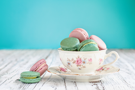 Antique Bavaria Winterling footed tea cup from the 1950s filled with pink strawberry and green tea macarons on a rustic white table against a teal background..