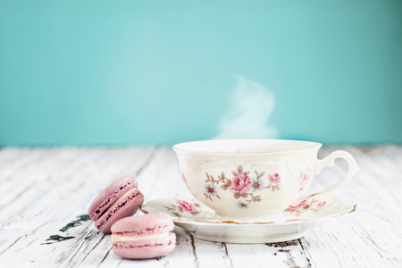 Antique Bavaria Winterling footed tea cup from the 1950s with pink macarons on a rustic white table against a teal background..
