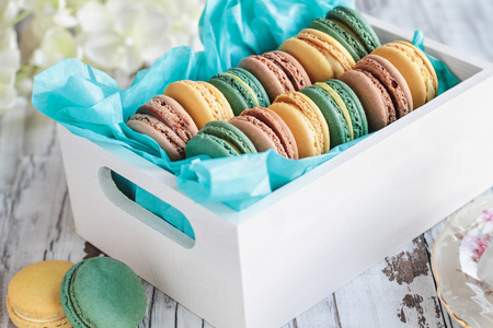 Assortment of fresh french macarons packaged in a pretty white wooden box with blue tissue on a white rustic table.. Stock Photo