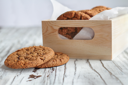 Box of fresh homemade oatmeal cookies on a white table against a white background.. Selective focus on two lying on table. Stock Photo