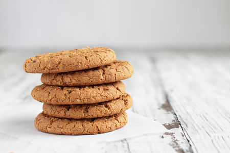 Stack of fresh homemade oatmeal cookies with a bottle of milk on a white table against a white background.. Stock Photo