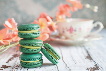 Stack of fresh french green tea macarons on a white rustic table with flowers and antique tea cup blurred in background.. Stock Photo