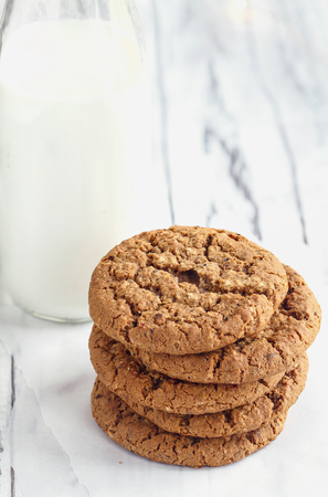Overhead shot of stack of fresh homemade oatmeal cookies with a bottle of milk on a white table against a white background.. Stock Photo