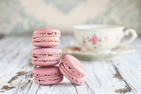 Stack of fresh french pink strawberry macarons on a white rustic table..