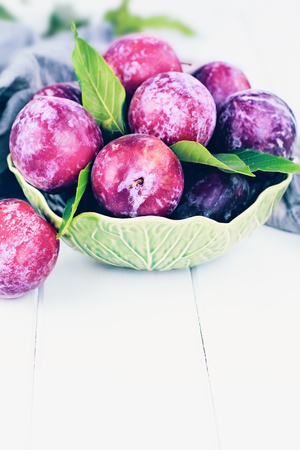 Freshly picked homegrown organic plums from the tree with leaves in a bowl.