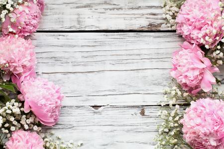 Pink Peonies and Baby's Breath flores sobre un fondo de mesa de madera rústica blanca con espacio para copiar el texto. Endecha plana.